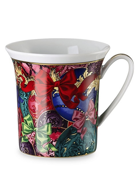 Image of From the Refections of Holidays Christmas Collection. This joyful ribbon print mug features Baroque elements that are unmistakably Versace. Porcelain. Hand wash. Made in Germany.