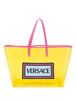 "Image of Playful translucent tote bag in a vibrant colorway and finished with a large Versace logo. Open top PVC Trim: Leather Imported SIZE Double top handles, 8.5"" 16"" W x 12.5"" H x 7"" D. Handbags - Italian Designers. Versace. Color: Yellow."