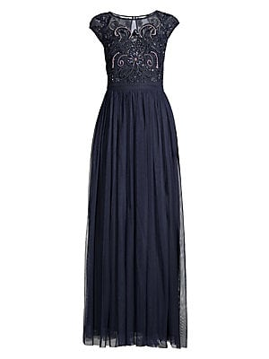 Image of A nineteen-twenties beaded bodice is paired with a flowing skirt for an entirely opulent look. Illusion roundneck Cap sleeves Beaded detail at the bodice Back button keyhole closure Back zip closure Fully lined Polyester Dry clean Imported SIZE & FIT Abou