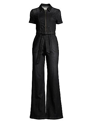 Image of An amalgamation of industrial cool and elegant flair, this denim jumpsuit was made for dramatic entrances with a flared silhouette. Spread collar Short rolled cuff sleeves Zip front Snap-button belt loops with self-tie waist Side slash patch pockets Fully