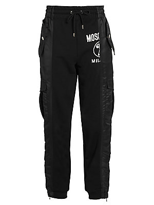 Image of Splicing together sweats with the cargo pant and a bit of track for good measure, these pants are an eye-catching number. A bisected Moschino logo underscores the quirkiness of the look. Elasticized drawstring waistband Belt loops Pull-on style Waist snap