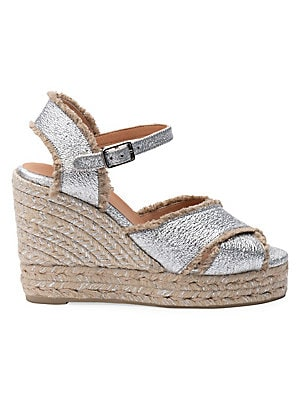 Image of Perfect for chic summer days and evenings, the Bromelia features a platform wedge with a criss cross font part an buckle closure. This is rendered in silver coated canvas. Coated linen upper Peep toe Buckled strap Fringe trim Leather lining Padded insole