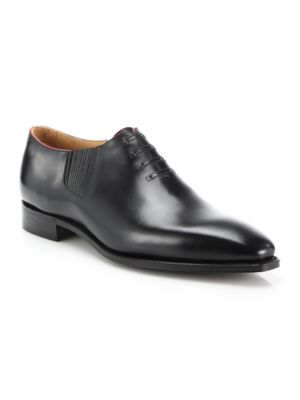 Image of EXCLUSIVELY AT SAKS FIFTH AVENUE. Hand-crafted from supple leather, these handsome dress shoes boast the look of a derby shoe with the ease of a slip-on for versatile style. Faux lace-up. Leather upper. Red piping. Leather lining. Padded insole. Goodyear