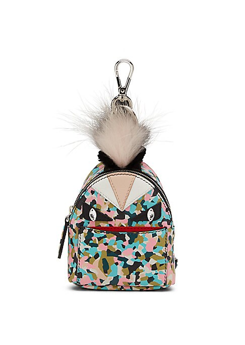 Image of Backpack-shaped key charm with fur and crystal detail. Silvertone lobster clasp and key ring. Leather. Fur type: Natural fox. Fur origin: Finland. Fur type: Dyed nutria. Fur origin: Argentina. Made in Italy.