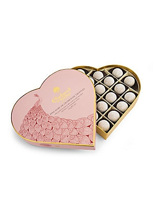 Image of An exclusive illustration for Charbonnel et Walker by Queen's scholar Kerry Lemon, our Pink Champagne heart makes a beautiful gift. Delectable pink truffles with a milk chocolate and Marc de Champagne centre, this heart shaped box is decorated with a peac