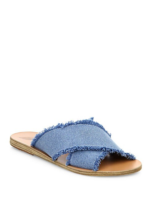 Image of Frayed light-wash denim casually styles crisscross slides. Fabric upper. Peep toe. Slip-on style. Leather sole. Made in Greece.