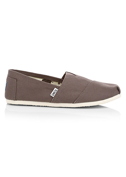 Image of Comfy canvas slip-on sneakers accented by seam details. Textile upper. Slip-on style. Rubbed sole. Imported. With every pair of shoes you purchase, TOMS will give a new pair of shoes to a child in need. One for One?