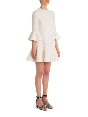 "Image of Wool-silk shift updated with feminine ruffled trim. Jewelneck. Three-quarter sleeves. Ruffled cuff and hem.A-line silhouette. Concealed back zip. About 33"" from shoulder to hem. Virgin wool/silk. Dry clean. Made in Italy. Model shown is 5'10"" (177cm) wear"