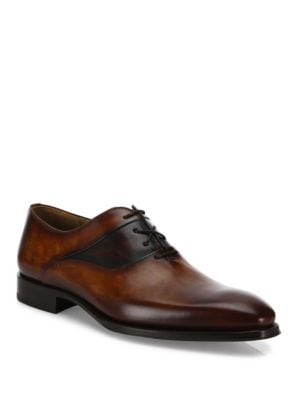 Image of EXCLUSIVELY OURS. Neatly crafted leather oxfords in dual tone finish. Calf leather upper. Wingtip toe. Crisscross lace-up style. Rubber sole. Made in Spain.