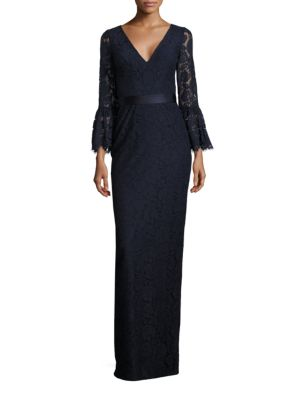 "Image of Alluring lace gown featuring floral and eyelet detail.V-neckline. Bell sleeves with scalloped cuffs. Banded waist. Concealed back zip closure. Center-back slit hem. Lined. About 63"" from shoulder to hem. Rayon/nylon/cotton. Dry clean. Imported. Model show"