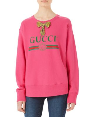 Image of An oversize sweatshirt with a Gucci print on the front, inspired by prints from the 1980s. The sweatshirt is further enhanced by a crystal-embroidered bow on the neckline. Rib-knit crewneck, cuffs and hem. Dropped shoulders. Long sleeves. Pullover style.