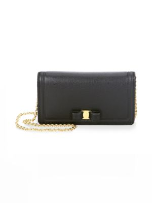 """Image of From the Vara Collection. Expertly crafted leather wallet features bow accent. Removable chain strap, drop 22"""".Button closure. Inside currency and flap pocket. Seven card chambers. Leather lining.7""""W x 4""""H x 1""""D.Leather. Made in Italy."""