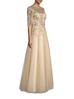 """Image of Elegant A-line gown with tonal floral embroidery. Illusion neckline. Elbow-length sleeves. Seamed waist. Flared skirt. Back button closure. Concealed back zip. Lined. About 63"""" from shoulder to hem. Polyester. Dry clean. Imported. Model shown is 5'10"""" (17"""