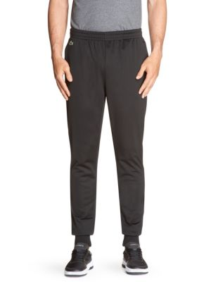 Image of Essential trackpants offer a comfortable solid finish. Elasticized waist with inner drawstring. Side slash pockets. Ribbed cuffs. Polyester. Machine wash. Imported.