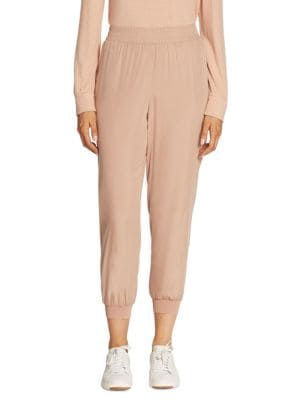 """Image of Easy smocked jogger pants in cropped silhouette. Smocked, elasticized waist. Smocked cuffs. Pull-on style. Rise, about 9"""".Inseam, about 27"""".Modal/polyester. Contrast: Viscose/elastane. Dry clean. Imported. Model shown is 5'10"""" (177cm) wearing US size Smal"""