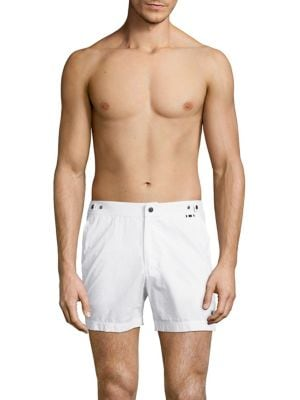 "Image of Cool swim trunks with dual side snap adjusters. Elasticized waist. Zip fly with snap button closure. Side slash pockets. Back right welt pocket. Rise, about 15"".Inseam, about 6"".Nylon. Machine wash. Made in Italy."