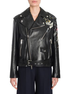"Image of Whimsical beaded tattoo embroidery elevates edgy biker jacket. Notch lapel. Shoulder epaulettes. Long sleeves. Zip cuffs. Asymmetrical zip front. Chest and waist zip pockets. Belted waist. Lined. About 25"" from shoulder to hem. Leather. Dry clean by leath"