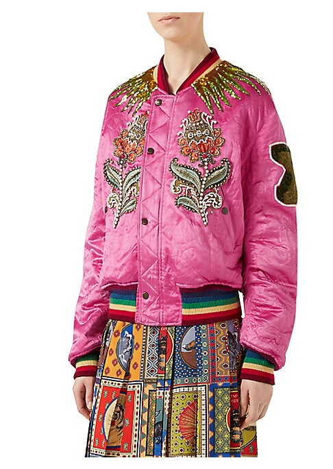 Image of The reversible bomber that on one side represents Gucci's distinct aesthetic with embellishments and elements that have become synonymous with the House. The tiger, one of Gucci's most recognizable codes, is paired with bursts of rays that emanate from th