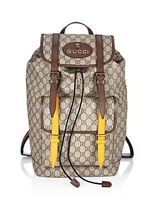 Image of A backpack made in soft GG Supreme, crafted from a coated microfiber fabric. The contrast buckles pay homage to the House's past, when artisans would repair luggage by replacing worn straps with new ones in any colors that were available. Top handle Adjus