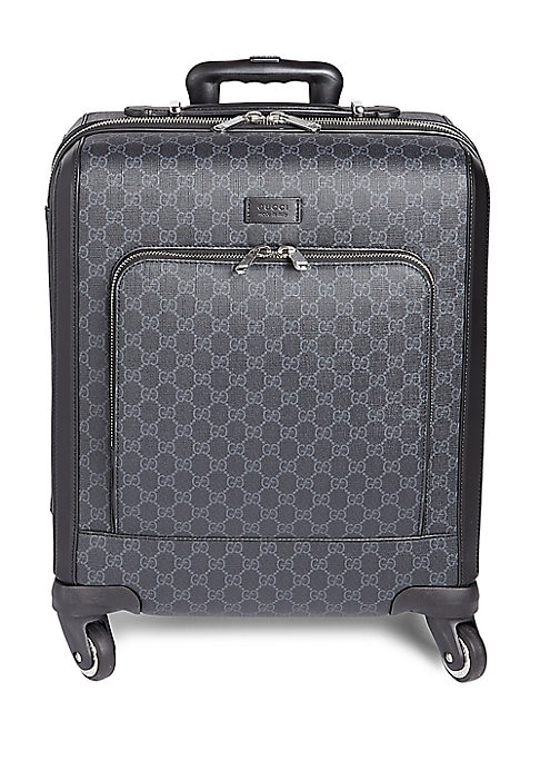 Image of A compact four wheel carry-on made in GG Supreme canvas. Retractable leather and telescopic top handles. Double zip closure with lock. Removable ID tag and key holder. Padded front exterior pocket with zipper closure. Four 360? wheels. Interior compartmen