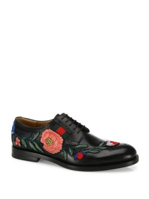 Image of A lace-up brogue shoe embellished with an embroidered floral applique-originally found on the Ace sneaker. The embroidery wraps around the shoe and ends with a bow at the heel. The shoe is further enriched with a grosgrain Web detail. Black leather upper