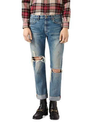 """Image of Special details that speak to the Creative Director's distinct design inspirations embellish pieces, linking them to the House. The back hem of this denim pant features a ribbon detail embroidered with the phrase """"L'Aveugle Par Amour."""" A now-iconic emblem"""