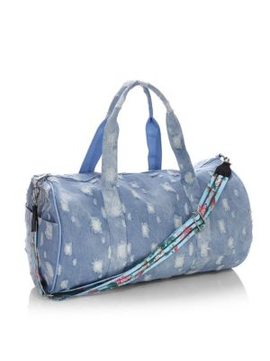 """Image of .Distressed duffle bag with floral shoulder strap. .Dual top handles. .Removable, adjustable crossbody straps. .Top zip cosure. .Two outside open pockets. .11""""W x 16"""" H x 11""""D. .Denim/cotton. .Spot clean. .Zip closure. ."""