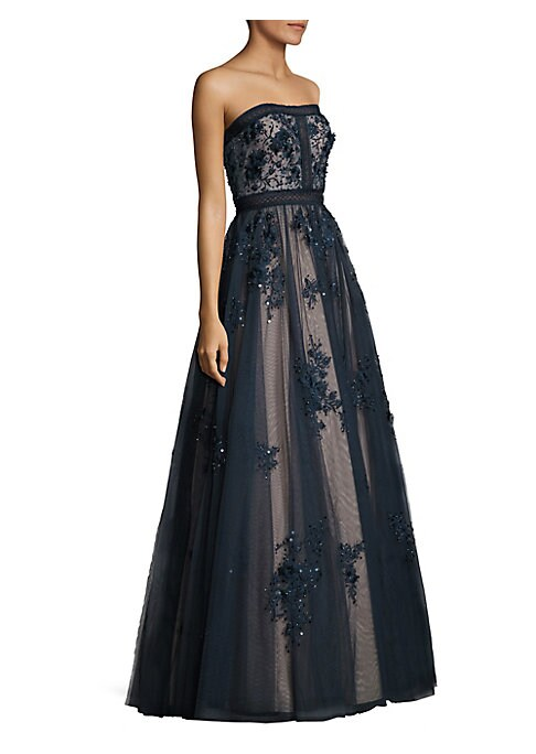 """Image of Eye-catching floral design updates this chic gown. Straight across neckline. Strapless. Concealed back zip. Asymmetrical hem. Lined. About 62"""" from top to hem. Polyester. Dry clean. Imported. Model shown is 5'10"""" (177cm) wearing US size 4."""