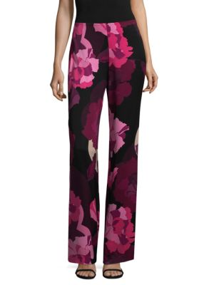"""Image of From the Netti Collection. Wide-leg pants featuring a chic floral print. No-waistband style. Rise, about 10"""".Inseam, about 29"""".Leg opening about 13"""".Rayon. Dry clean. Made in USA of imported fabric. Model shown is 5'10"""" (177cm) wearing US size 4."""