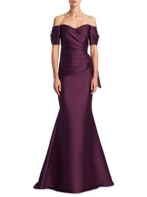 "Image of .Mermaid gown with pleated and bow at back details. .Sweetheart neckline. .Off-the-shoulder. .Short sleeves. .Concealed back zip. .About 62"" from shoulder to hem. .Polyester/spandex. .Dry clean. .Imported. .Model shown is 5'10"" (177cm) wearing US size 4."