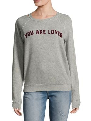 """Image of Raglan cotton sweatshirt with printed design at chest. Roundneck. Long raglan sleeves. Ribbed cuffs and hem. Distressed details. About 24"""" from shoulder to hem. Cotton. Machine wash. Made in USA. Model shown is 5'10"""" (177cm) wearing size Small."""