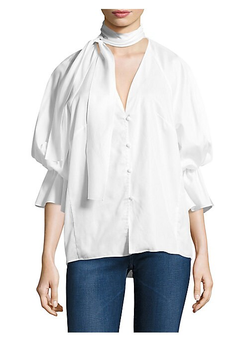 """Image of Cotton top with self-tie at neck and ruffle details.V-neck. Short puff sleeves. Button front. Slim-fit. About 24"""" from shoulder to hem. Cotton. Dry clean. Made in USA of imported fabric. Model shown is 5'10"""" (177cm) wearing size Small."""