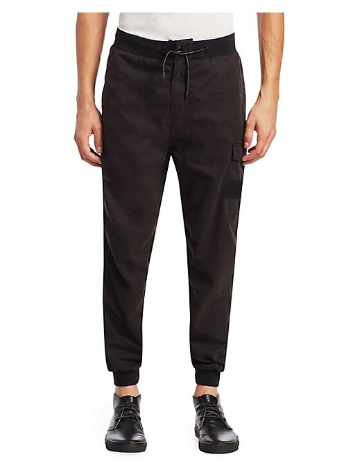 Image of EXCLUSIVELY OURS. Cotton-blend jogger pants with drawstring waistband. Elasticized drawstring waist. Button closure. Side slant pockets. Cargo side flap pocket. Back patch pocket. Back zip pocket. Banded at leg openings. Regular-fit. Rise, about 11.Inseam