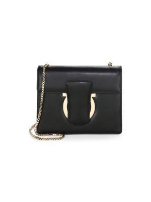 "Image of Signature details enhance sleek, polished crossbody. Chain strap, 20"" drop. Magnetic flap closure. Goldtone hardware. Interior slip pocket. Two interior compartments.8""W x 6""H x 1.5""D.Leather. Made in Italy."