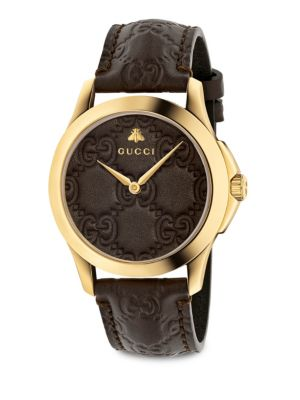 """Image of From the G-Timeless Collection. This watch features a Gucci signature detail throughout. Swiss quartz movement. Round case, 38mm (1.5"""").Gold-tone PVD stainless steel. Leather strap. Leather dial. Analog. Made in Switzerland."""