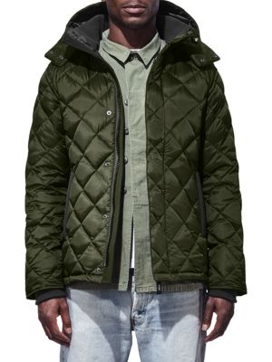 Image of Down-filled coat with warm quilted exterior. Attached hood. Stand collar. Long sleeves. Concealed front zip. Logo patch at sleeve. Front snap closure. Side welt pockets. Hi-lo hem. Lined. Nylon/polyester/cotton. Fill: Down. Dry clean. Made in Canada.