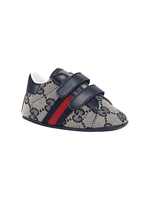 Image of Gucci logo and Web adorns sneakers. Canvas and leather upper. Round toe. Grip tape closure. Textile lining. Rubber sole. Padded insole. Made in Italy.