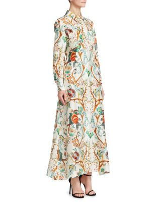 """Image of Long sleeve silk shirt dress in intricate flower print. Point collar. Button front closure. Long sleeves with button cuffs. Chest patch pockets. Slip pockets at waist.58"""" shoulder to hem. Silk. Dry clean. Made in Italy. Model shown is 5'10"""" (177cm) wearin"""