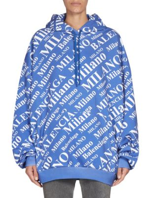 """Image of Milano print adorns stretch hoodie. Attached drawstring hood. Long drop shoulder sleeves. Rib-knit cuffs and hem. Front pouch. Pullover style. About 25"""" from shoulder to hem. Cotton. Machine wash. Imported. Model shown is 5'10"""" (177cm) wearing US size Sma"""
