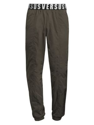 "Image of On-trend pants with contrasting brand logo on waist. Elasticized waistband. Elasticized cuffs. Front slash pockets. Back welt pocket. Rise, about 11"".Inseam, about 33"".Leg opening, about 10"".Polyester. Dry clean. Imported."