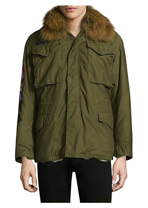 Image of Luxe fur collar and lining elevates enduring military coat. Oversized spread collar with attached fur. Shoulder epaulettes. Long sleeves. Button cuffs. Zip front with snapped storm placket. Chest flap patch pockets. Waist flap pockets. Interior drawstring