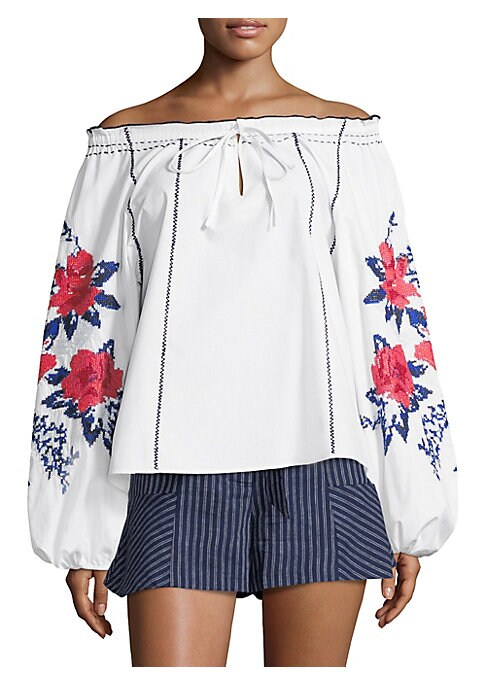 """Image of Airy off-the-shoulder blouse with floral embroidery. Off-the-shoulder. Front tie detail. Long sleeves. Pullover style. About 25"""" from shoulder to hem. Cotton. Dry clean. Imported. Model shown is 5'10"""" (177cm) wearing US size Small."""