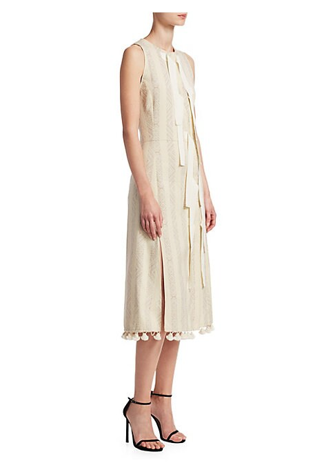 """Image of Asymmetric trim and side slit offers deconstructed aesthetic to dress. Crewneck. Sleeveless. Asymmetric snap-button front. Attached dangling ribbons. Right side slit. Tassel hem. About 45"""" from shoulder to hem. Cotton/polyester. Dry clean. Made in italy."""