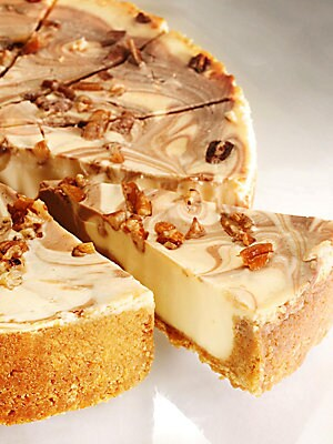 Image of A creamy caramel-infused filling swirled with chocolate and topped with pecans all nestled in our famous Honey-Graham-Pecan Crust. Caramel cream cheese filling Hershey's chocolate swirl Topped with pecans 8 Inch cake Serves 8-10 people Allergen Warning: P