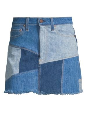 """Image of Denim mini skirt with patchwork design. Belt loops. Zip fly with button closure. Five-pocket style. Fringe hem. About 18"""" long. Cotton/elastane. Machine wash. Made in USA of Italian fabric. Model shown is 5'10"""" (177cm) wearing US size 4."""