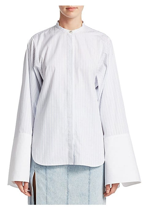 """Image of Oversize pinstripe shirt with band collar and statement cuffs. Band collar. Long sleeves with oversize cuffs. Front button closure. Shirttail hem.24"""" shoulder to hem. Cotton. Dry clean. Made in USA. Model shown is 5'10"""" (177cm) wearing US size 4."""