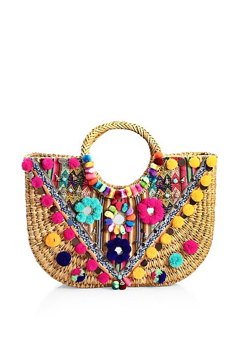 "Image of Boho basket tote with vibrant floral and pom pom embellishments. Double top handles, 8.5"" drop. Open top.14""-16.5""W x 10""H.Straw/acrylic/iliclla. Imported."