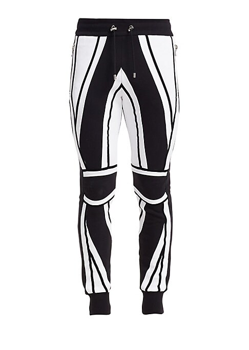 Image of Bold tapered pant with contratsing moto inspired panelling. Elatsicized waist. Waist zip pockets. Tapered leg. Banded ankle. Cotton. Dry clean. Made in France.