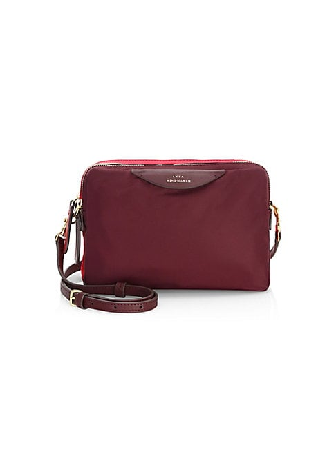 """Image of Compact mini bag with stacked compartments and sleek leather trim. Adjustable, removable crossbody shoulder strap. Top zip closures. Goldtone hardware. Three inside card slots. Lined. Nylon/leather. Imported. SIZE.7""""W x 5""""H x 3""""D."""