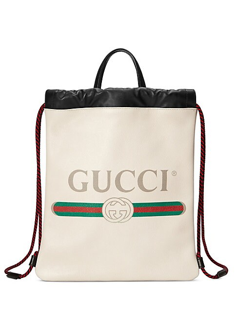 "Image of Gucci Print small drawstring backpack. Double leather handles, 3"" drop. Rope straps that double function as a drawstring. Gucci vintage logo. Interior pouch. Unlined.12""W x 14""H.Leather. Made in Italy."